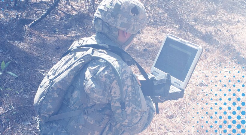 Military personnel using a military grade laptop computer in the field
